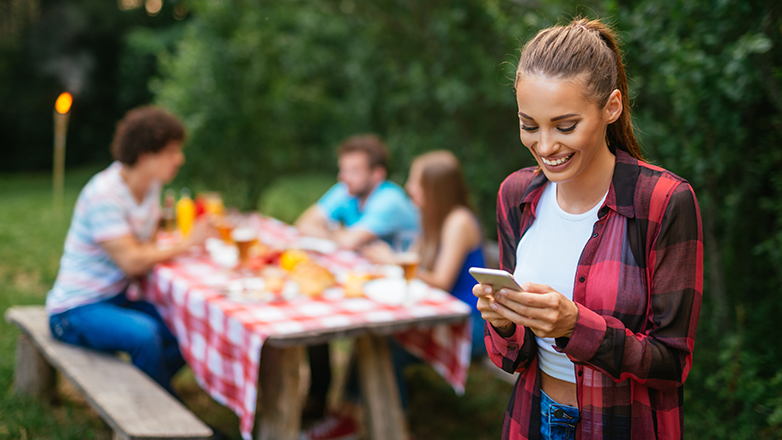 Female enjoying a picnic looking at her phone