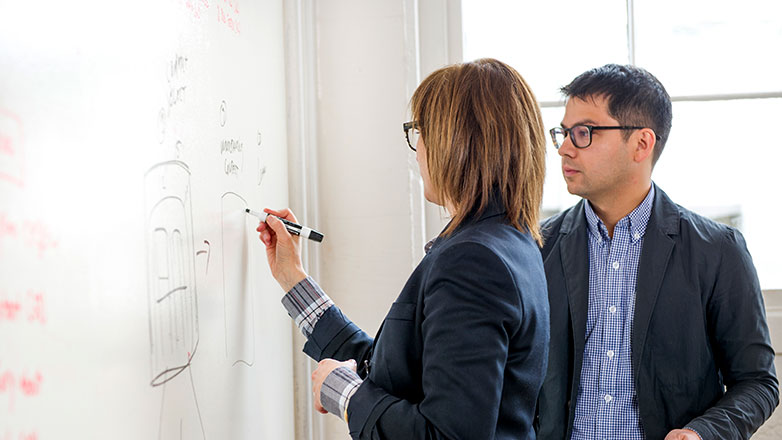 Male and female coworkers writing on whiteboard.