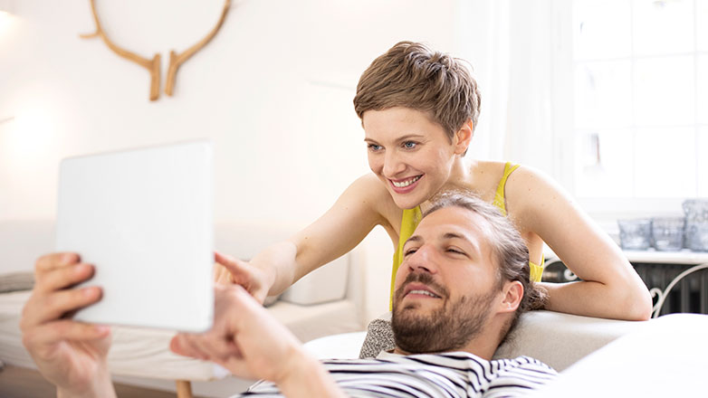 Man laying on couch with woman over his shoulder searching on an ipad.