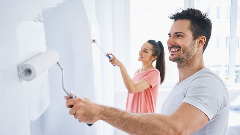 Couple smiling as they paint the walls in their new home.