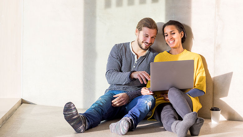 Young couple sitting on their apartment floor looking at their laptop.