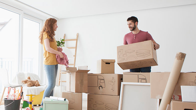 Couple standing in their new home surrounded by boxes from their move.