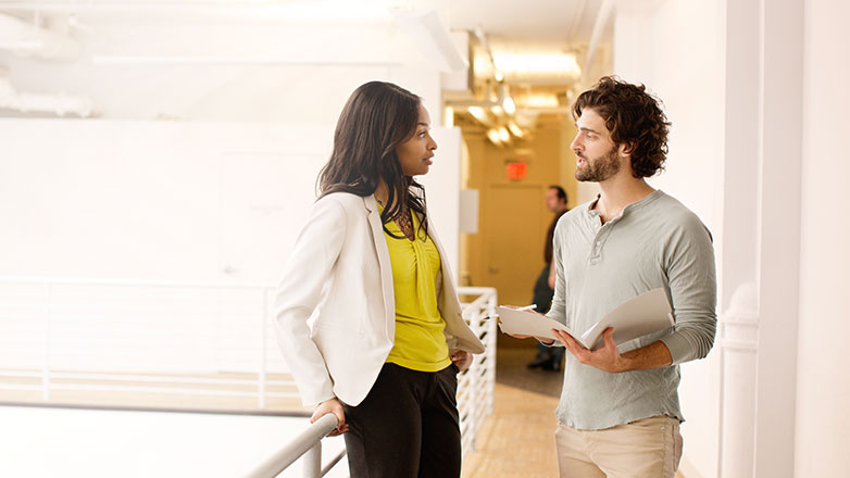 Male and female standing in a company hallway having a discussion.