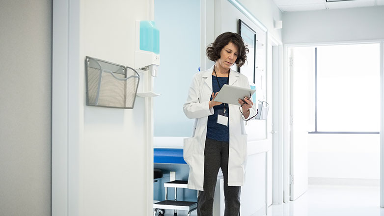 Female doctor looking at a chart in a hallway of a hospital.