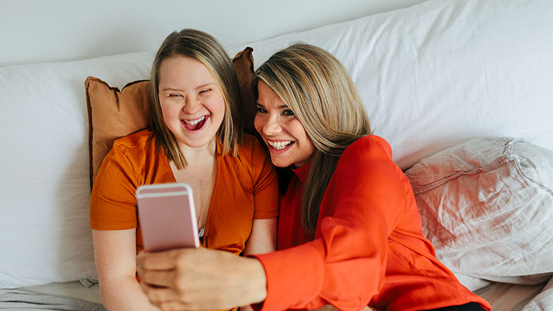 Mom and adult daughter having fun laying in bed taking a selfie.