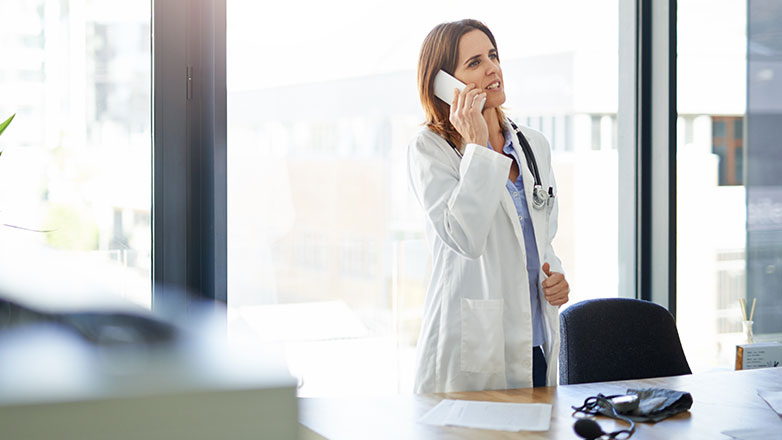 Female physician standing behind her desk in a hospital talking on the phone.