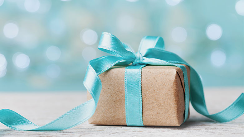 Gift box wrapped in brown paper and blue bow.