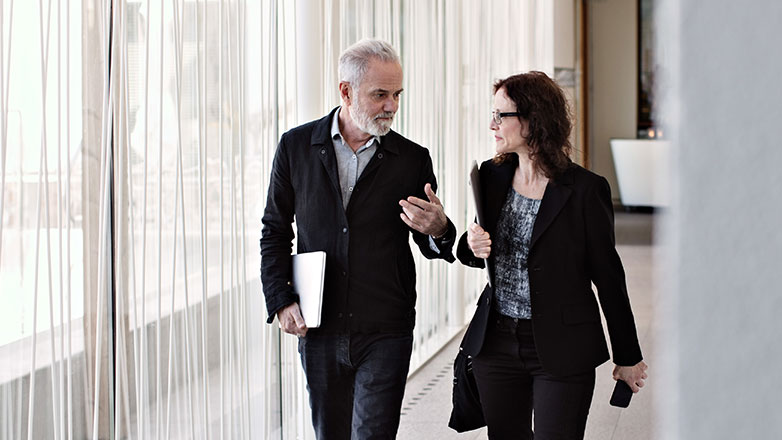 A man and woman discussing strategy as they are walking to their meeting.