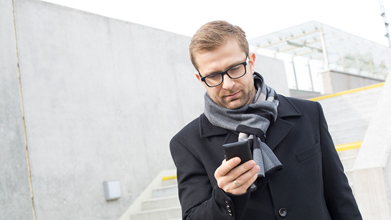 Man outside dressed in winter coat looking at his phone while standing on the stairs.