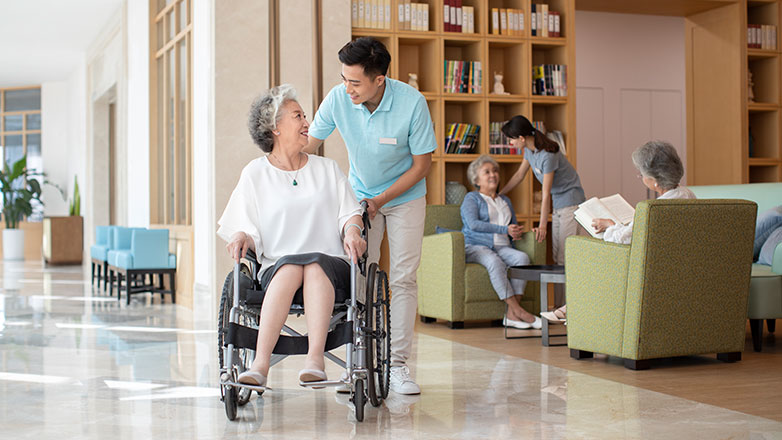 Woman in wheelchair is being helped by a male assistant in the lobby of a nursing home.