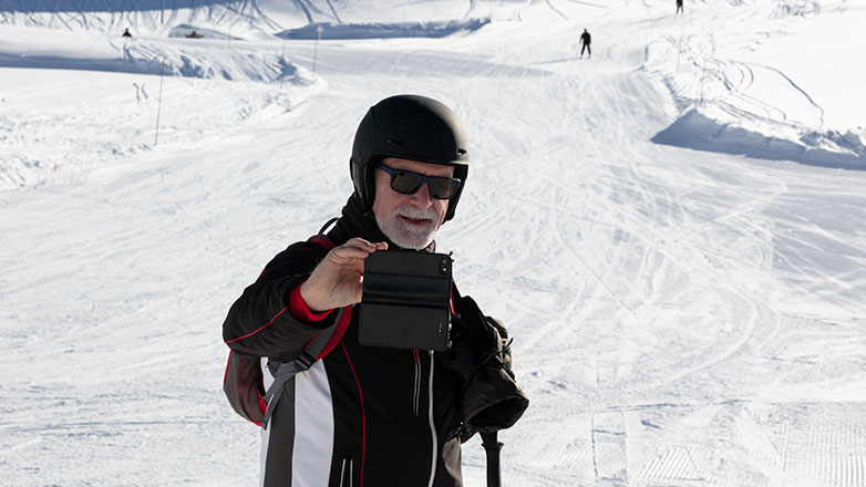 Older man taking a selfie at the bottom of a ski hill.