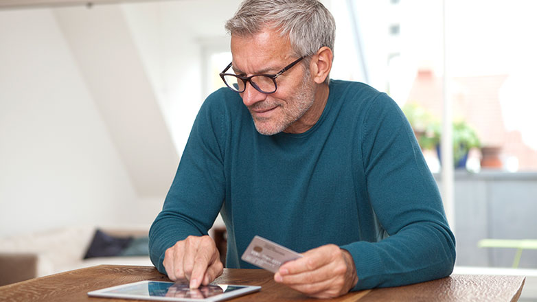 Man at home using his debit card to make an online purchase.