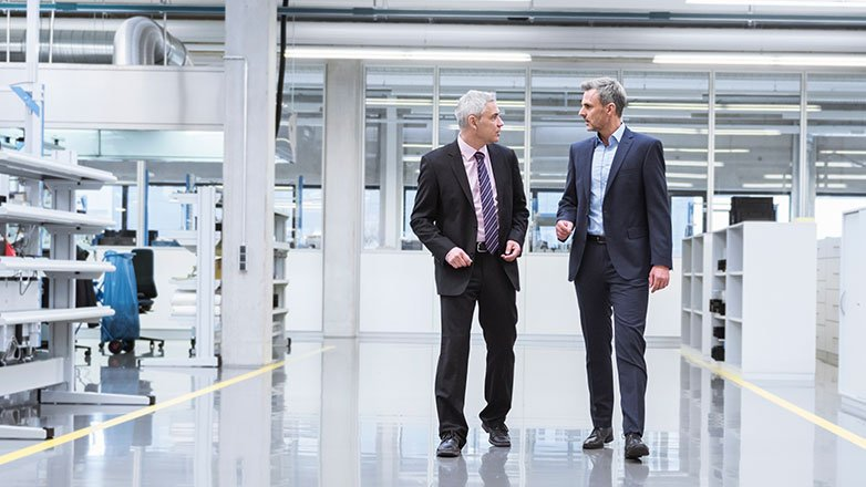Two men in a manufacturing facility having a discussion.