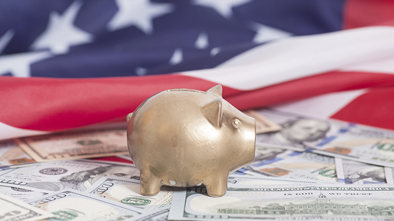 piggy bank  on money in front of american flag