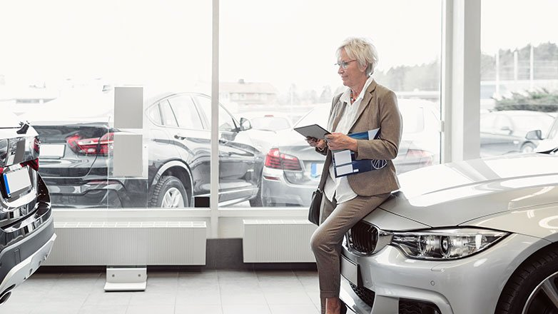 Woman at the car dealership purchasing a new car.