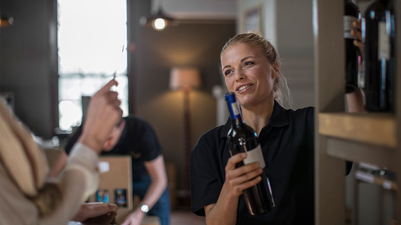 Cashier handing over a wine bottle to a customer making a purchase.