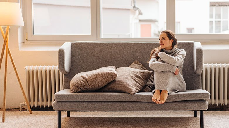 Woman sitting alone on her couch.