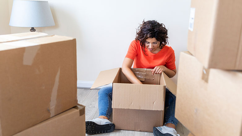 Woman sitting on the floor surrounded by boxes.