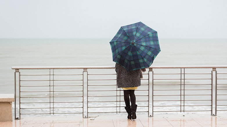 Woman standing with umbrella overlooking the water.