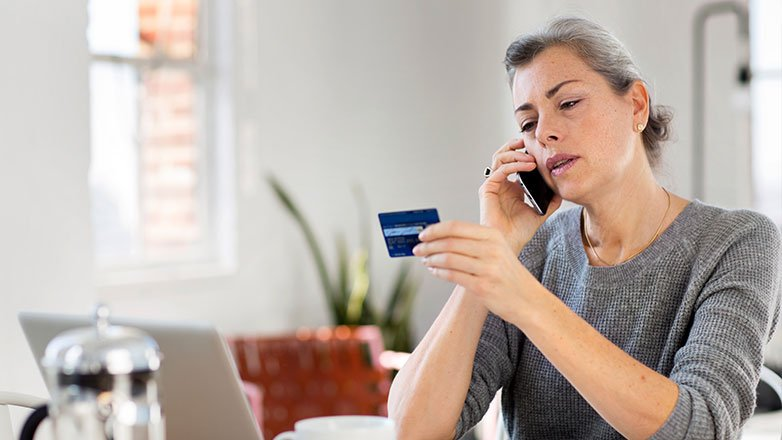 Woman sitting at table using credit card to order online.