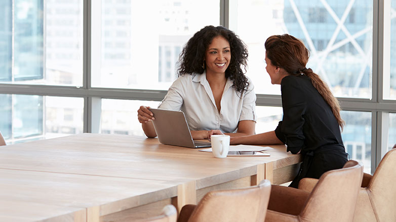 Two professional women sitting at a boardroom table talking with laptop in front of them.