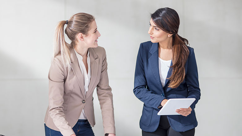 Two professional females standing at a desk talking to each other.