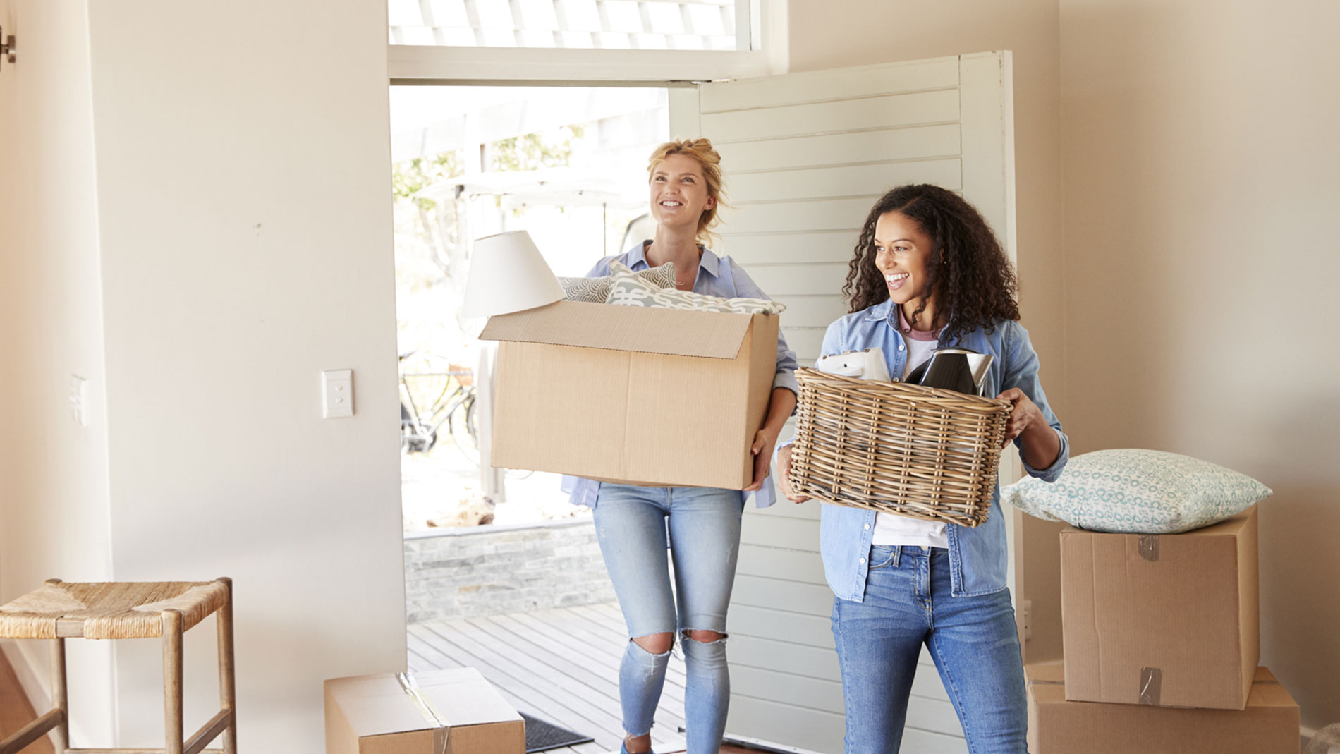 two women carrying boxes into new home
