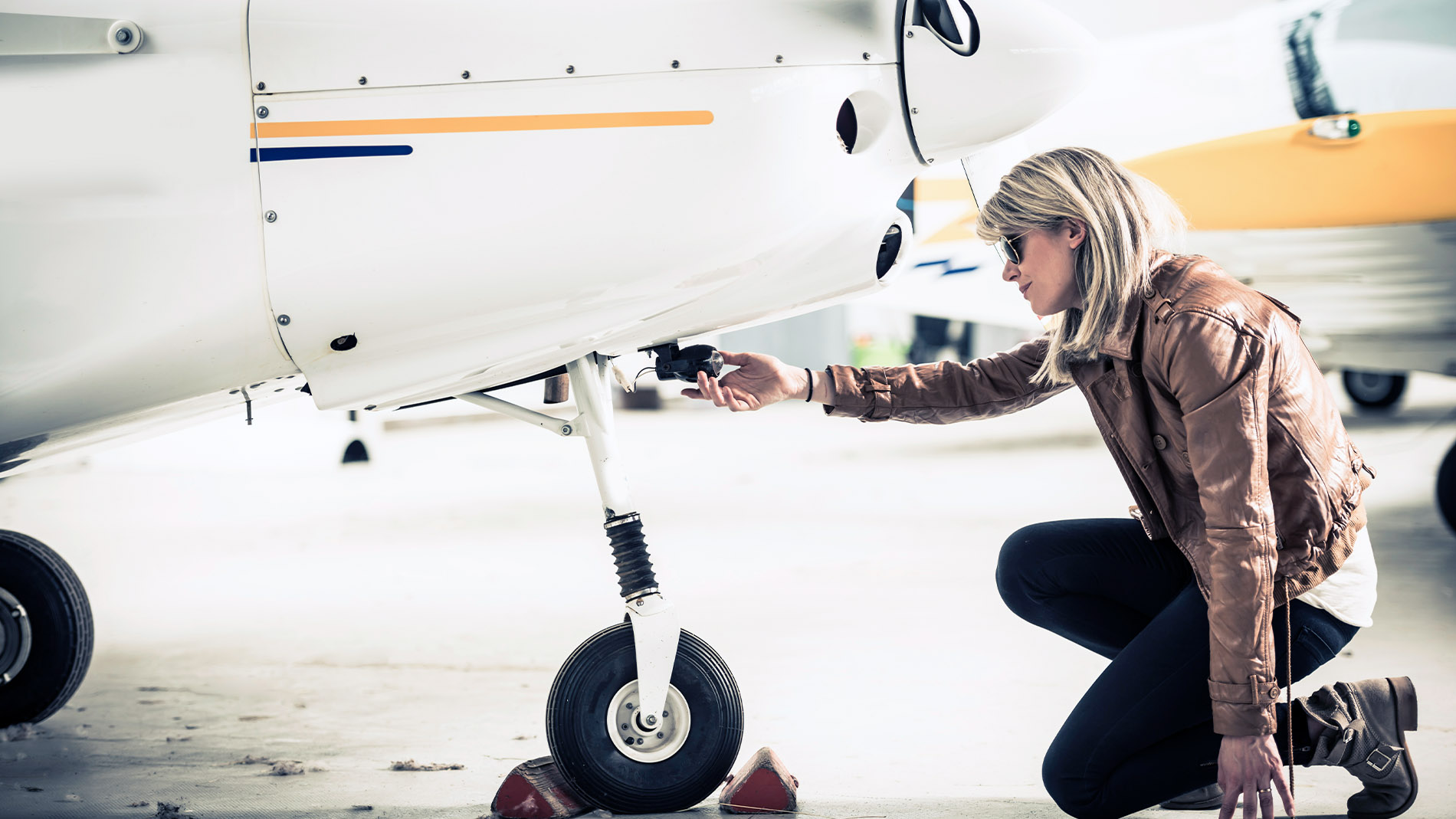 female-pilot-inspecting-plane-wheel