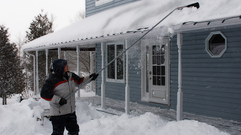man shoveling snow off of the roof.