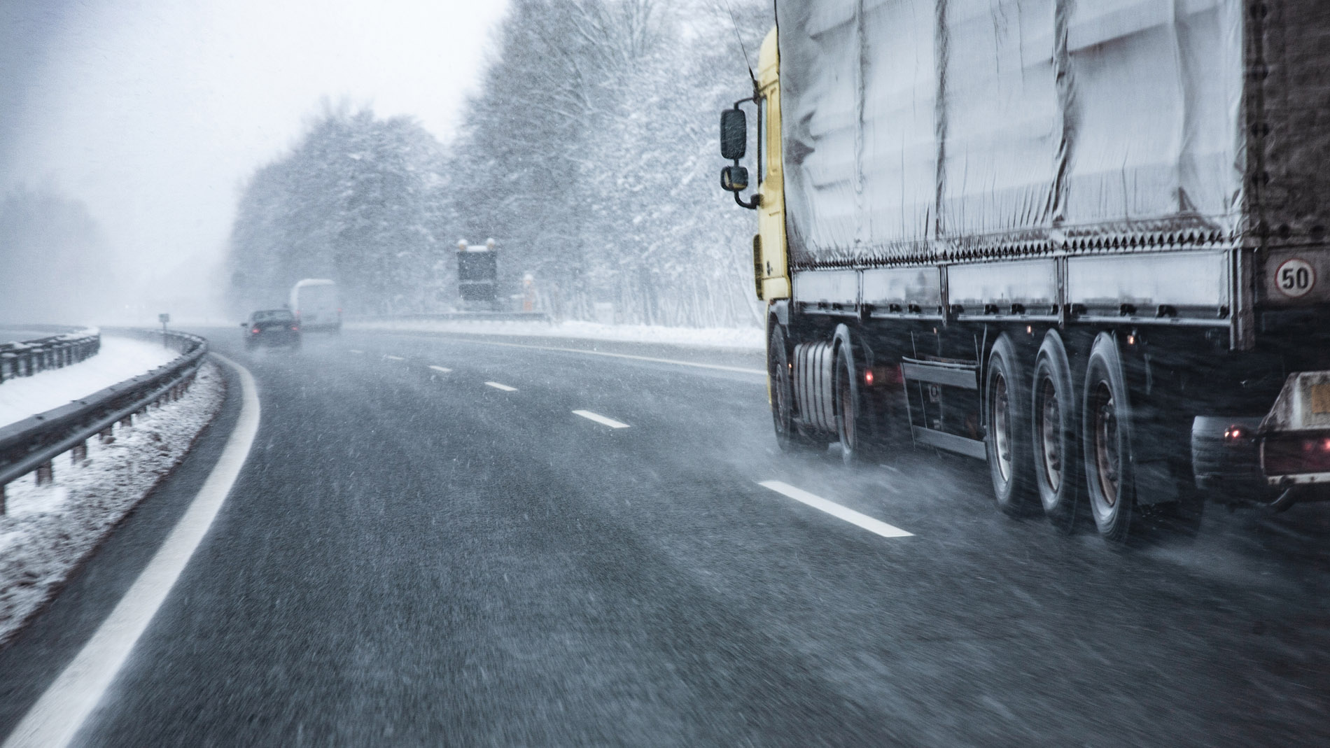 truck driving in snowy treacherous road conditions