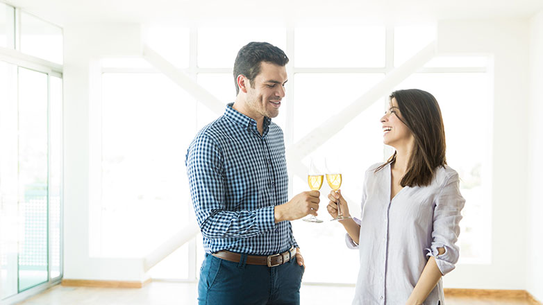 Couple celebrating with champagne in an empty house.