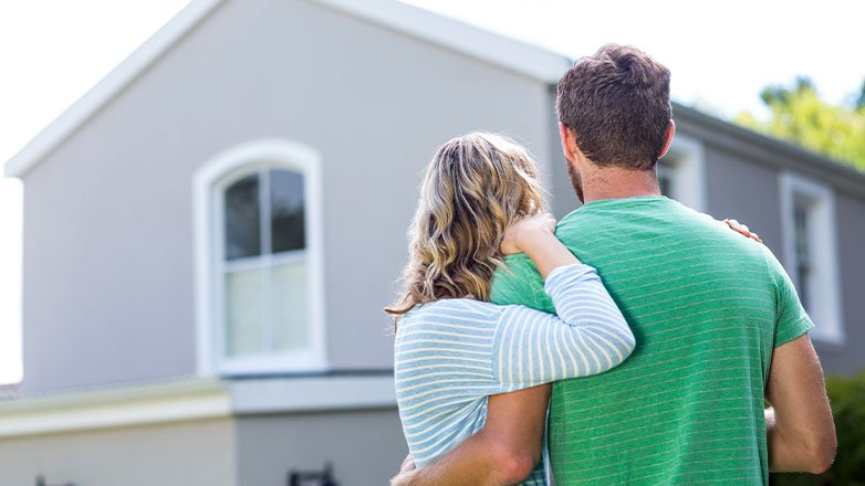 couple holding arms looking away towards house