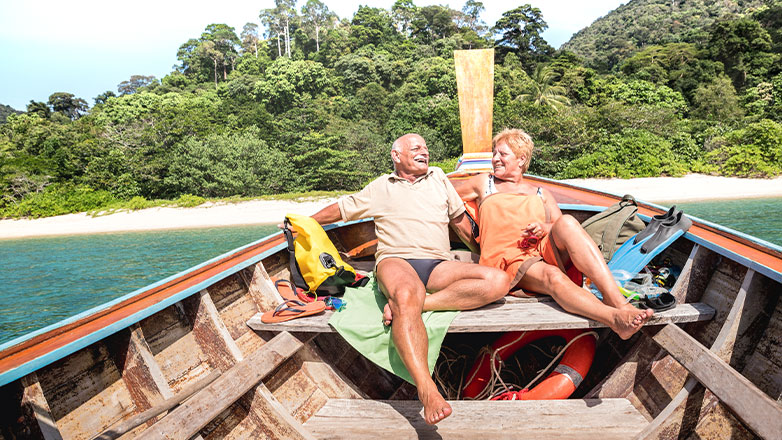 couple sitting in wooden boat off cost of beach