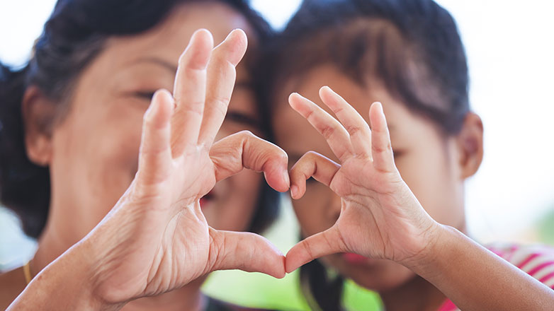 Mom and daughter put their hands together to make a heart.