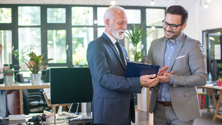 father teaching son business practices on clipboard in office