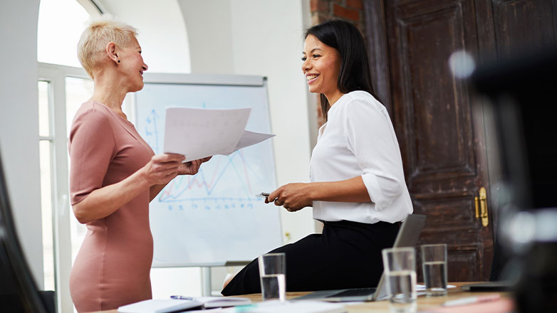 female coworkers smiling and discussing paperwork and graph on large board