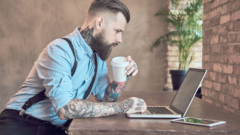 man drinking coffee seriously looking at laptop on desk