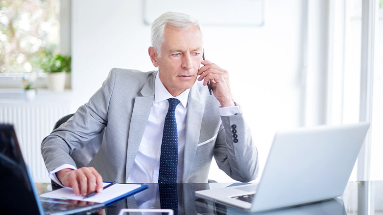 man on phone at desk looking at computer