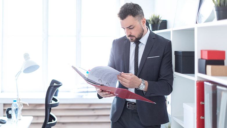 man standing by desk paging through binder