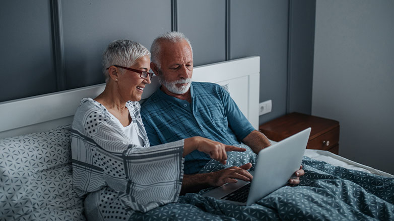 old couple sitting in bed pointing and working on laptop