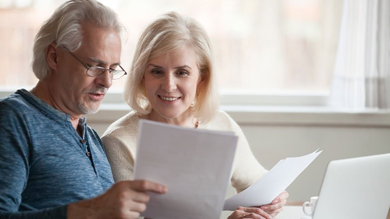 older couple finalizing paperwork at desk with computer