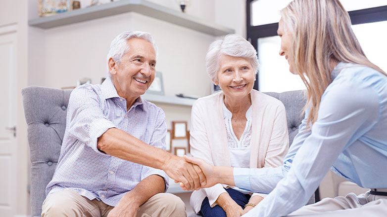 older man and woman shaking hands with woman across table