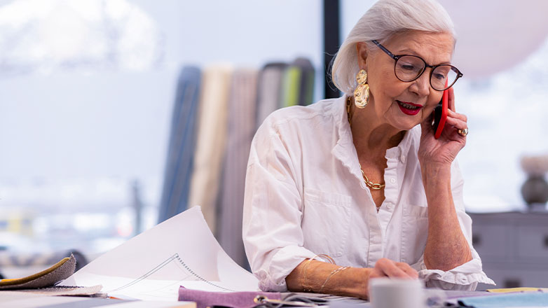 older woman on phone doing professional work at desk
