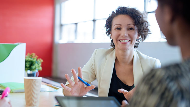 smiling woman holding pen meeting with client