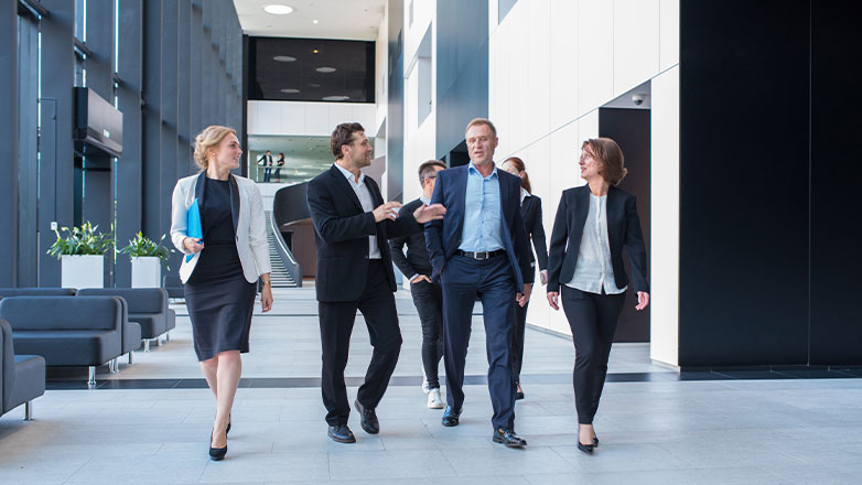 team of employees walking together down office hallway